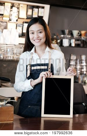 Young asian women Barista holding blank chalkboard with smiling face at cafe counter background small business owner food and drink industry concept