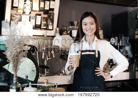 Young asian women Barista holding a take away coffee cup with smiling face at cafe counter background small business owner food and drink industry concept