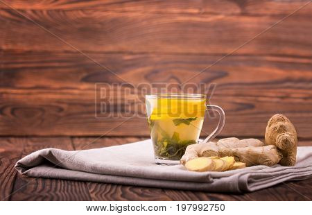 A close-up of a glass tea cup full of yellow beverage on a dark wooden background. A cup of beverage, cut lemon, ginger and green tea leaves on a gray table-cloth. Winter healthful tce. Copy space.