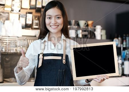 Young asian women Barista holding blank chalkboard and thumb up gesture with smiling face in font of cafe counter background small business owner food and drink industry concept