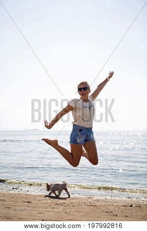 girl in sunglasses and short shorts jumping on a beach