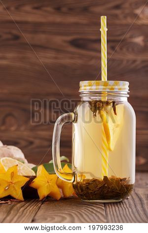 A glass with a bright yellow straw filled with bright natural hot beverage on a wooden background. A tasty and healthy drink next to ginger, carambola, mint,  and cut lemon in a mason jar. Copy space.