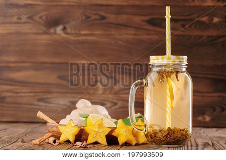 A close-up of a glass jar with a straw full of yellow vitamin beverage on a wooden background. A tasty and healthy drink next to ginger, carambola, cinnamon and cut lemon in a mason jar. Copy space.