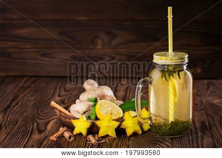 A close-up of a glass jar with a bright straw full of yellow herbal beverage on a dark wooden background. A tasty and healthy drink next to ginger, mint leaves, cinnamon, carambola and cut lemon.