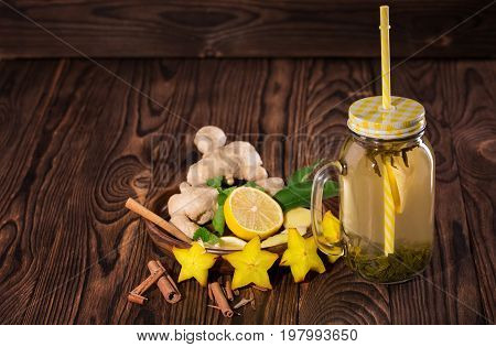 A close-up of a glass mason jar with a straw full of yellow herbal beverage on a dark wooden background. A tasty and healthy drink next to ginger, mint, carambola, cinnamon and cut lemon. Copy space.