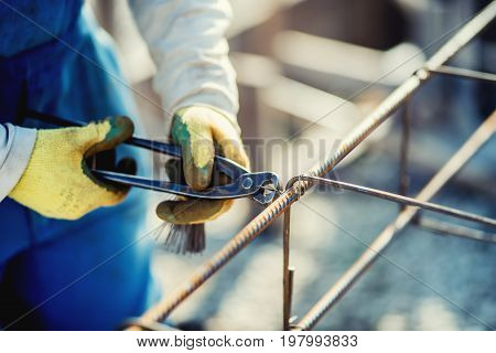 Details Of Construction Workers Hands Securing Steel Bars With Wire Rod For Reinforcement Of Concret