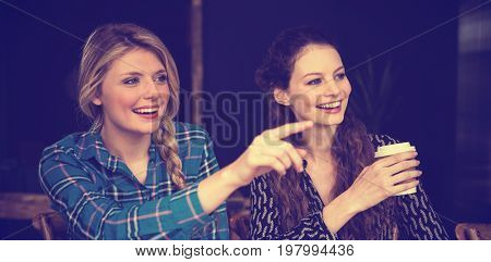 Smiling young woman showing something to friend at coffee shop