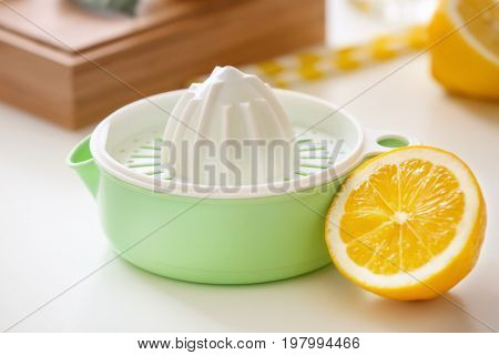 Plastic squeezer and half of lemon on white table