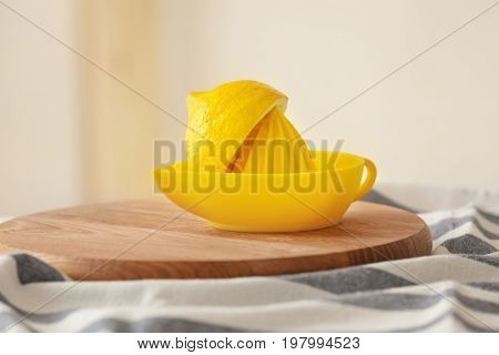 Cutting board with squeezer and fresh lemon on table