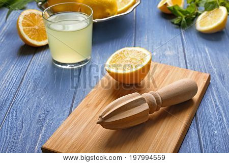 Cutting board with squeezer, glass of juice and lemons on wooden table