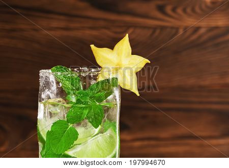 Close-up of a highball glass full of summer mojito cocktail from mineral water, sugar, rum, juice limes, ice and mint leaves on a wooden table. Summer, refreshing and alcoholic cocktails. Copy space.