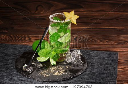 A glass of alcoholic mojito on a dark brown wooden background. A cold drink with rum, mint,  sugar, lime, decorative carambola and ice cubes on a black table-cloth. Summer drinks. Copy space.