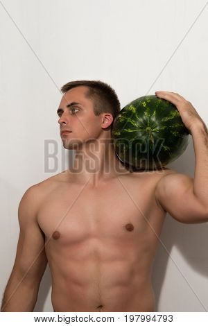 The guy is holding a huge watermelon on his shoulder. A guy with a bare torso on a light background.