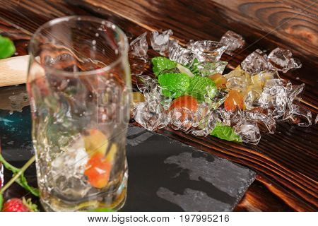 Close-up of crystal ice cubes on a dark wooden background. Glistering cubes next to ripe grapes, bright mint twigs,  and highball glass. Natural ingredients for summer beverages. Alcoholic cocktails.