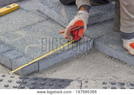Paver Measuring Irregular Space For Laying Concrete Brick