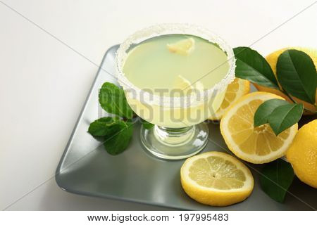 Platter with glass of juice and lemons on white background
