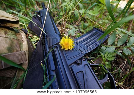Military helmet rifle and a flower in the grass. Soldier military stop war war and peace paintball concept