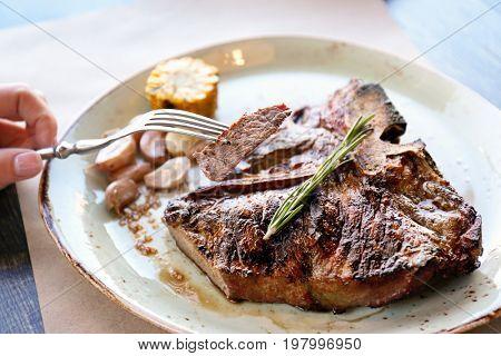 Slice of beefsteak on fork over plate