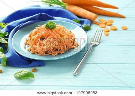 Plate with delicious carrot raisin salad on wooden table