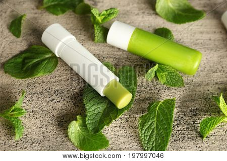 Hygienic lipstick with lemon balm on textured background