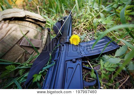 Military Helmet, Rifle And A Flower In The Grass Close Up