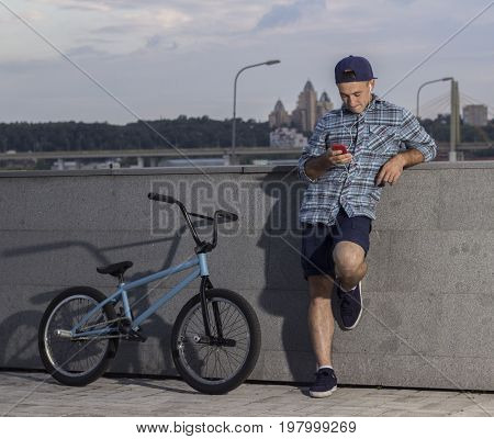 bmx rider taking a pause during a training session on the bmx and listen to music on the background of the city