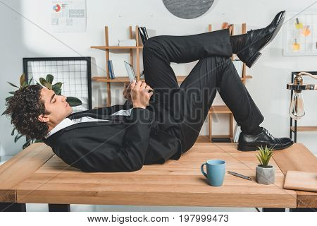 Side View Of Young Businessman Lying On Table And Using Tablet In Office