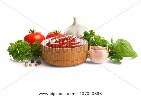 Wooden bowl with sauce, greenery, spices and tomatoes on white background