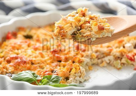 Wooden spoon with piece of delicious turkey casserole, closeup