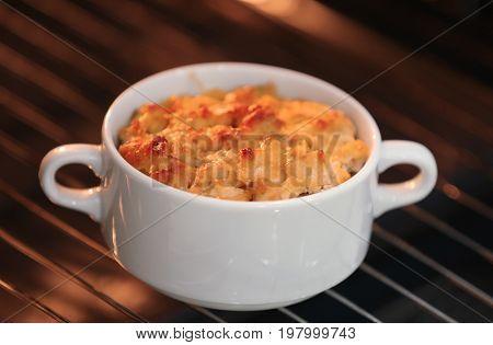 Ceramic pot with turkey casserole in oven, closeup