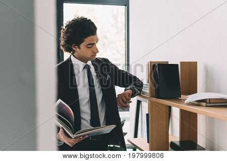 Portrait Of Businessman Checking Time On Wrist Watch While Reading Book In Office