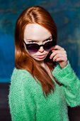 young redhead girl in greem pullover and sunglasses over dark blue background. beauty model woman with luxurious red hair. hairstyle. holiday makeup poster