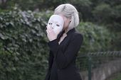 Young blond girl taking off a mask. Pretending to be someone else concept. outdoors poster