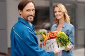 Providing services. Handsome gallant energetic man meeting young lady while doing his job and delivering products from vegetable store poster