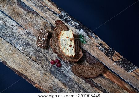 Top View Of Assorted Fresh Baked Bread In Slices On Wooden Planks With Few Grapes.