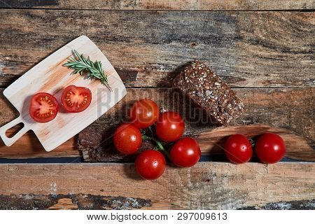 Arrangement Of Shiny Ripe Tomatoes On Branch With Wholegrain Bread On Wooden Planks