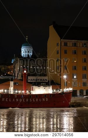Helsinki, Finland - February 18, 2019: Ship In Frozen Harbour And Main Helsinki Cathedral In The Bac