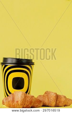 Paper Cup Of Coffee And Croissants On A Yellow Background, Copy Space