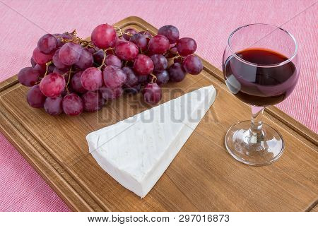 Glass Of Red Wine, Triangular Piece Of Brie Cheese And Red Sweet Grapes On Brown Wooden Cutting Boar