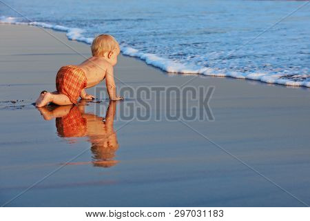 On Sunset Beach Funny Baby Boy Crawling By Water Pool To Sea Surf For Swimming In Waves. Family Trav