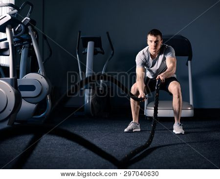 Muscular Man is Doing Battle Rope Exercise while Working out in Dark Modern Training Fitness Gym. Cr