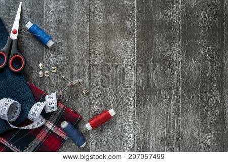 Sewing Accessories, Jeans And Plaid Fabric On A Dark Wooden Background. Fabric, Sewing Threads, Need