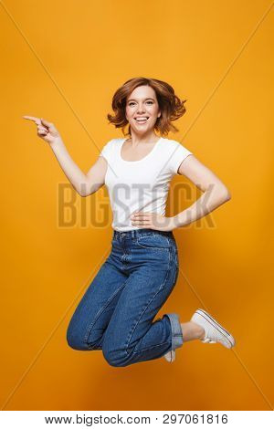 Full length portrait of a happy lovely girl jumping isolated over yellow background, pointing at copy space
