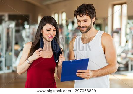 Handsome personal trainer with his client looking at clipboard at the gym