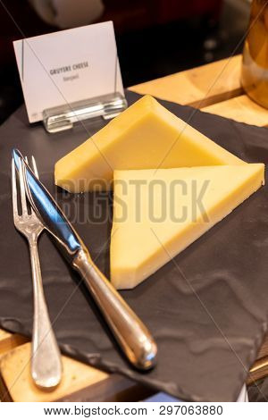 gruyere cheese on black stone plate in buffet line
