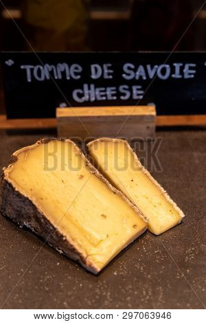 tomme de savoie cheese on rustic wooden table in buffet line