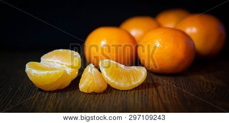 Clementine Slices And Whole Clementines On A Table
