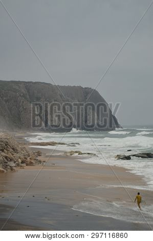 Person Leaving Evil After Surfing On A Cloudy Day At Playa Grande In Colares. Nature, Architecture,