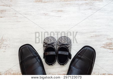 Fathers Business Black Shoes And Daughters Baby Black Shoes On Rustic White Wood Background. Concept