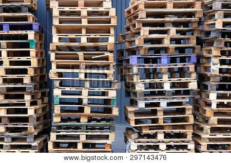 Stacks Of Colorful Rough Wooden Pallets At Warehouse In Industrial Yard. Pallets Background. Cargo A
